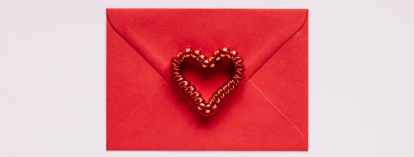 colorful gift envelope with heart on pink background